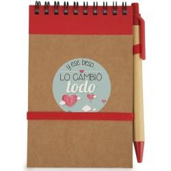 Libreta roja con bolígrafo rojo y adhesivo frase